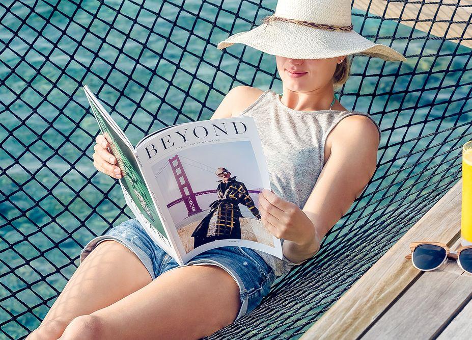 woman enjoying read magazine in maldives st regis photo by mediatropy